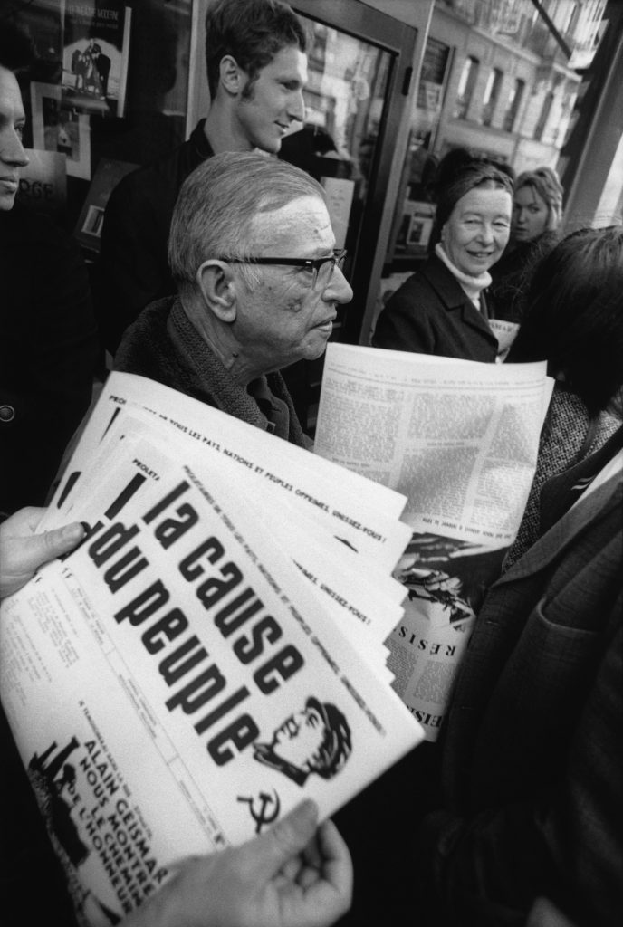 "Le philosophe Jean-Paul Sartre avec Simone de Beauvoir (au fond, le regardant en souriant) distribuant le journal maoïste ""La Cause du Peuple"", interdit par le gouvernement français, à Paris en 1970. (© Bruno Barbey/Magnum Photos)"