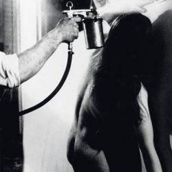 Yves Klein détourant un corps de femme à l'eau lors d'une anthropométrie au cours de la réalisation d'une peinture de feu.