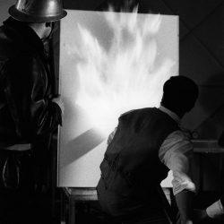 Yves Klein réalisant une peinture de feu, tandis qu'un pompier se tient prêt à arroser la toile pour l'empêcher de prendre entièrement feu.