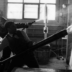 Yves Klein réalisant une peinture de feu, tandis qu'un pompier arrose la toile pour l'empêcher de prendre entièrement feu.